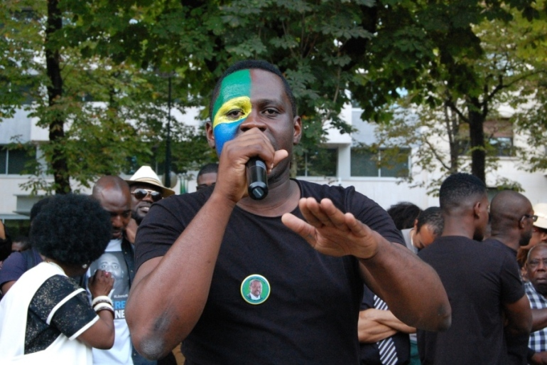 Cool Mpassy interpelle la foule une fois la marche arrivée devant l'ambassade. Crédit : Sana Sbouai